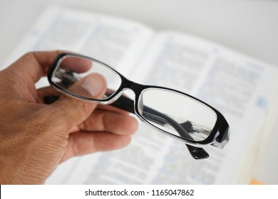 Hand holding eye glasses with blurry book on background