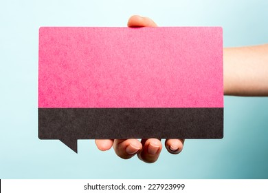 Hand holding female pink speech bubble on blue background. Woman concept.