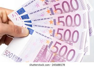 Hand holding five hundred euros bills against white background