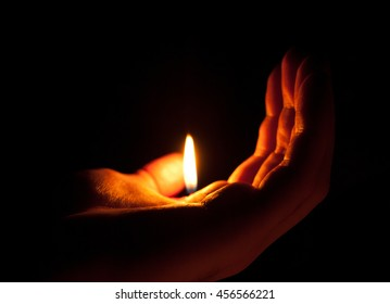 Hand holding a flame in the dark (shallow DOF, selective focus)