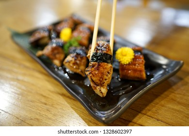 Hand holding foie gras sushi using chopsticks - A plate of steamed rice topped with grilled goose liver and sweet sauce on wooden table, Traditional Japanese Food.