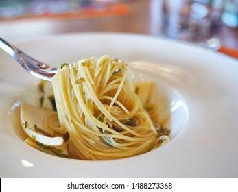 Hand holding fork Italian & Japanese fusion cold and refresing al dente angel hair pasta with triangular or pizza slice-shaped Abalone with seaweed ponzu Sauce served in ceramic white hat dinner plate