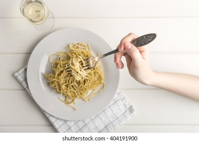 Hand holding fork with pasta and glass of white wine on white background