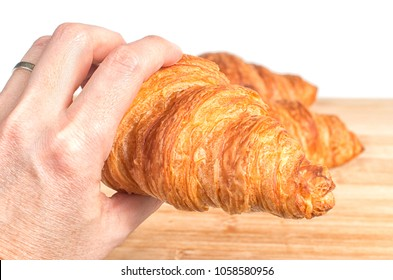 Hand holding a fresh French croissant isolated on white background