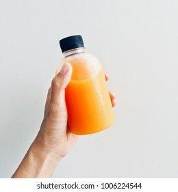 Hand holding fresh and healthy orange juice in a bottle isolated on a white background