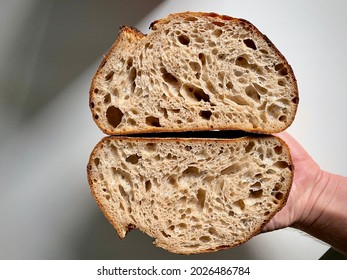 A hand holding a freshly cut loaf of delicious sourdough bread