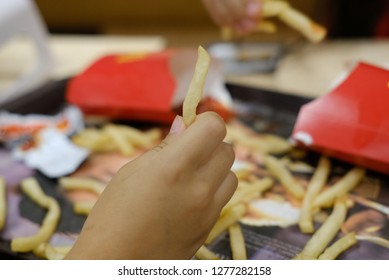 Hand holding fried potatoes in a fast food cafe closeup photo