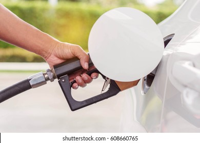 hand is holding the fuel tank at the gas station.