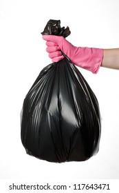 Hand holding a full black plastic trash bag