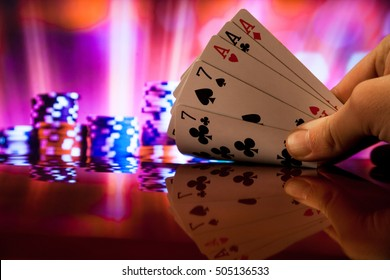 Hand holding full house poker cards combination on blurred background casino luck fortune