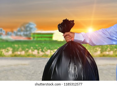 Hand is holding a garbage bag everyday garbage,carrying,on sunlight background