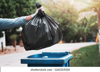 hand holding garbage black bag putting in to trash