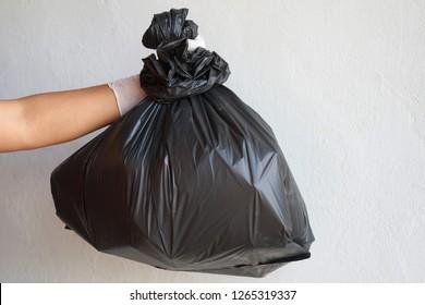 hand holding garbage black bag isolate on white background