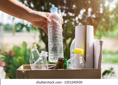 hand holding garbage bottle plastic putting into recycle bag for cleaning