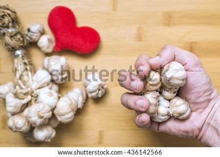 hand holding garlic for Lower high blood pressure. Herbal healthy. Concept