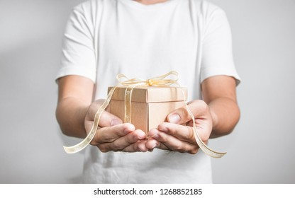 Hand holding gift box with golden ribbon