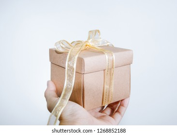 Hand holding gift box with golden ribbon, Birth day concept, Happy new year