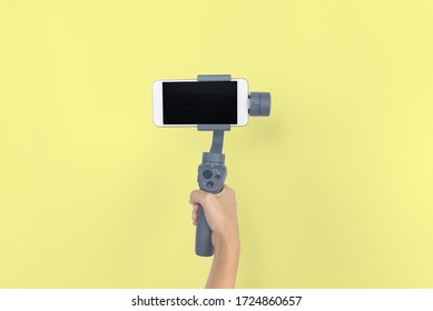 Hand holding gimbal or stabilizer with mobile phone on yellow pastel background. Vlog and travel concept. copy space. Video mobile.