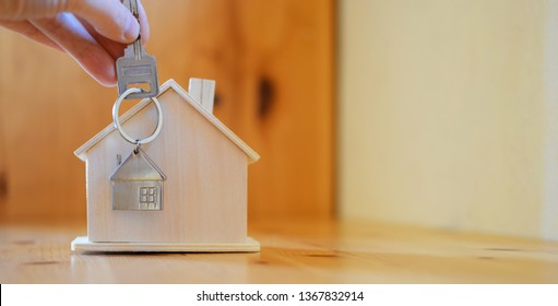 Hand holding giving key chain with house shaped pendant on blurred wooden table and home model background with copy space. Real estate, buying moving new home, renting property or apartments concept.