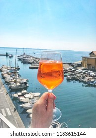 A hand holding a glass of aperol spritz over the sea