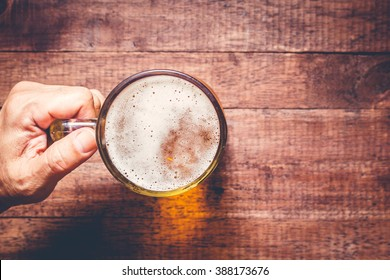 Hand holding a glass of beer on wooden table