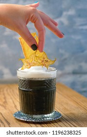 hand holding glass with black cocktail of cuttlefish ink, alcohol, cream with carom