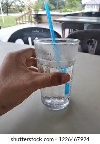 Hand holding a glass of cold plain water.