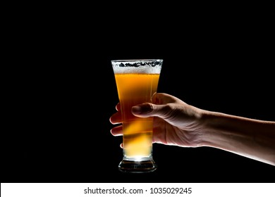 Hand holding glass of craft beer on black background