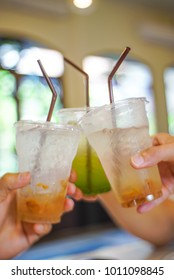 hand holding a glass of italian sodas iced beverage sweet and salty plum and kiwi syrup flavour refreshment cheers drink