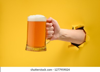 Hand holding a glass pint of craft beer through a ripped hole in yellow paper wall. Alcohol drink with thick froth head.