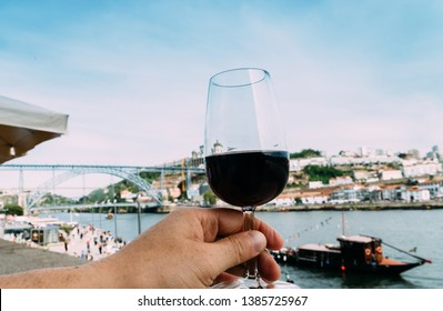 Hand holding glass of red wine overlooking Cais da Ribeira and Ponte de Dom Luis I on the River Douro in Porto, Portugal