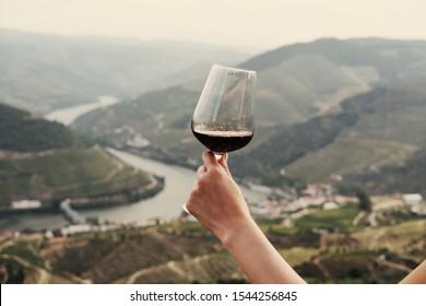 Hand, die ein Glas Rotwein hält auf dem Hintergrund Landschaft des Douro-Tals, Portugal. Produktionsstätte für Portwein