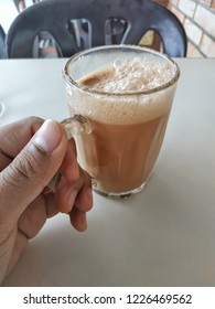Hand holding a glass of sweet hot milk tea with foam on the top.