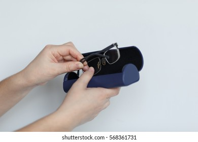 Hand holding glasses and blue case isolated on white background.