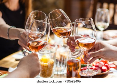 Hand holding glasses with rose wine over a table rich with Balkan and Moldovan cuisine dishes