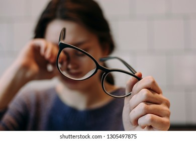 A hand holding glasses. Tired young girl on the background.