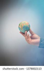 Hand holding a globe