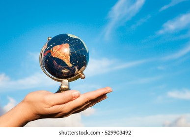 Hand holding globe against a beautiful blue sky. World travel concept.