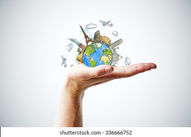 Hand holding a globe with landmarks
