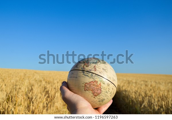 A hand holding up a globe withAustralia and South East Asia facing the camera with a field of wheat out of focus against a deep blue sky.