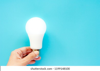 Hand holding glowing LED light bulb on blue background for energy savings concept