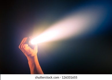 hand holding glowing pocket torch light