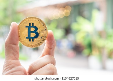 Hand holding gold bitcoin in front of restaurant that accepted bitcoin to pay for service online.digital currency.technology lifestyle