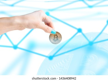 Woman's hand holding gold coin bitcoin on background of blockchain concept.