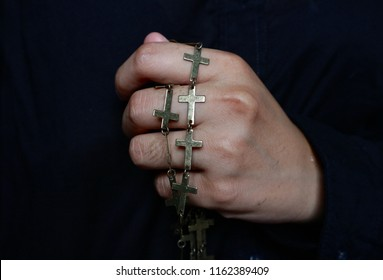 Hand holding gold cross necklace in black background