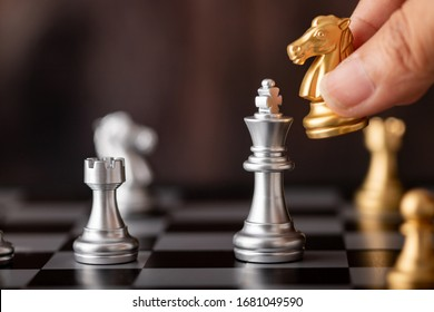 hand holding gold horse attack silver king in game on the chessboard with wooden background