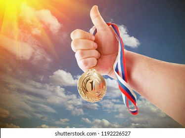 Hand holding gold medal on sky background with sunlight