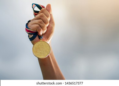 Hand holding gold medal on sky background, The winner and successful concept
