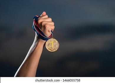 Hand, die eine Goldmedaille auf bewölktem, dunklem Hintergrund hält, Der Gewinner und das erfolgreiche Konzept