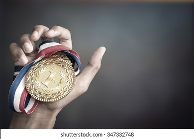 hand holding up a gold trophy cup/ medal as a winner in a competition